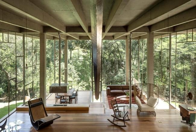 Modernes Haus aus Glas und Beton im Regenwald errichtet geräumiges Wohnzimmer hohe Glaswände Blick ins Freie
