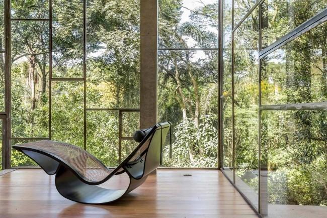 Modernes Haus aus Glas und Beton im Regenwald errichtet schicker Schaukelsessel ein Mix aus modernem und Retro Design
