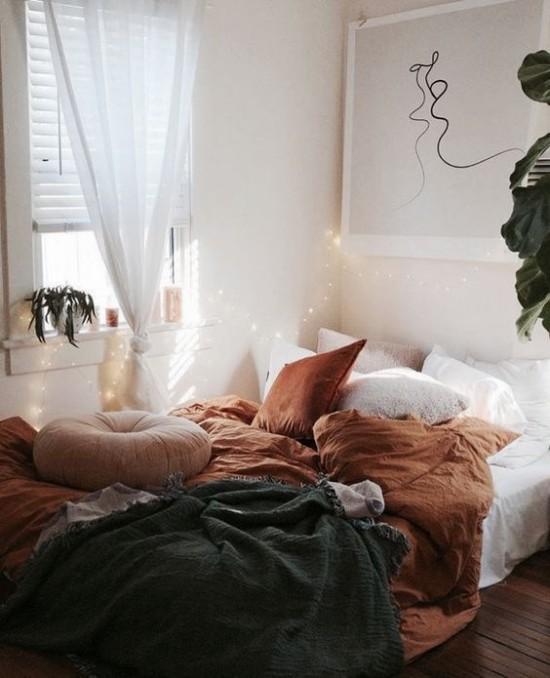 Schlafzimmer herbstlich gestalten Bettbezug in warmen Herbstfarben Brauntöne und Türkis Sonnenlicht und Lichterkette