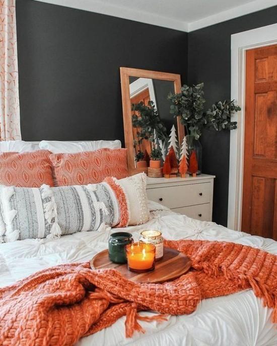 Schlafzimmer herbstlich gestalten Kontrast dunkle Wand in Schwarzgrün Bettwäsche in Weiß Wurfdecke in Lachsfarbe Holz Kissen Zimmerpflanze