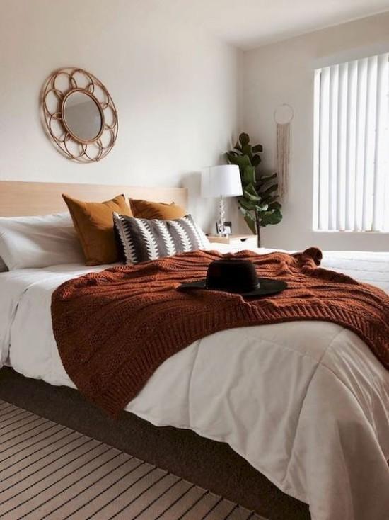 Schlafzimmer herbstlich gestalten gemütliche Atmosphäre Kontrast zwischen Weiß und Dunkelbraun schwarzer Filzhut grüne Zimmerpflanze Ecke