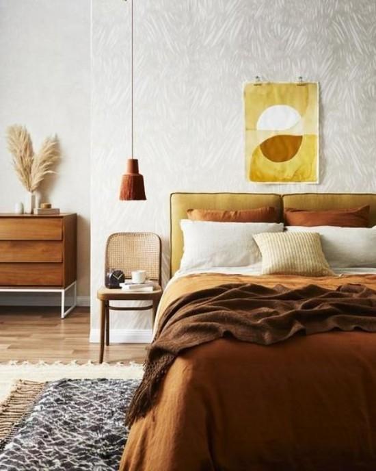 Schlafzimmer herbstlich gestalten gemütliche Atmosphäre Wanddeko Gelb Braun Bettzeug in Ocker und Schokoladenbraun