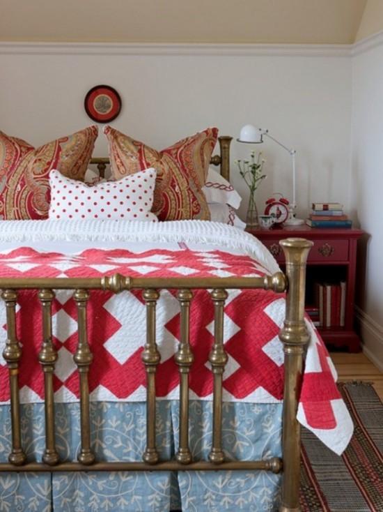 Schlafzimmer herbstlich gestalten rustikales Ambiente Bettzeug in Rot und Weiß gemusterte Kissen Nachtisch Lampe Bücher