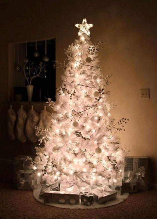 Weihnachtsbaum schmücken in Weiß und Silber Stern alle Lichter angezündet schöner Blickfang im dunklen Zimmer