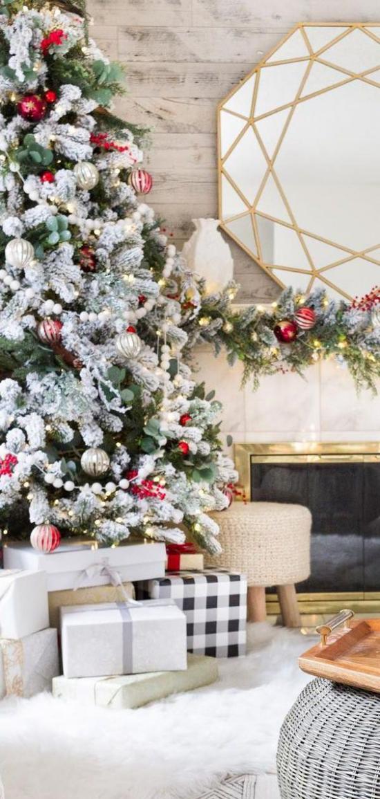 Weihnachtsbaum schmücken in Weiß und Silber glänzende rote Kugeln weiße Girlanden klassischer Look