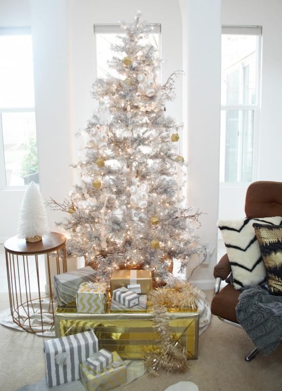 Weihnachtsbaum schmücken in Weiß und Silber goldglänzende Kugeln viele schöne verpackte Geschenke unter dem Baum