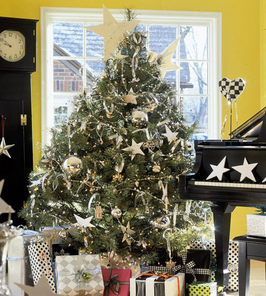 Weihnachtsbaum schmücken in Weiß und Silber klassischer Christbaum goldener Schmuck zahlreiche verpackte Geschenke neben dem Klavier