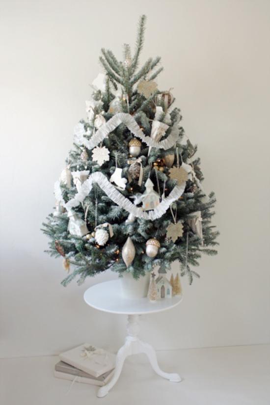 Weihnachtsbaum schmücken in Weiß und Silber kleiner Christbaum auf kleinem runden Tisch platziert schön dekoriert