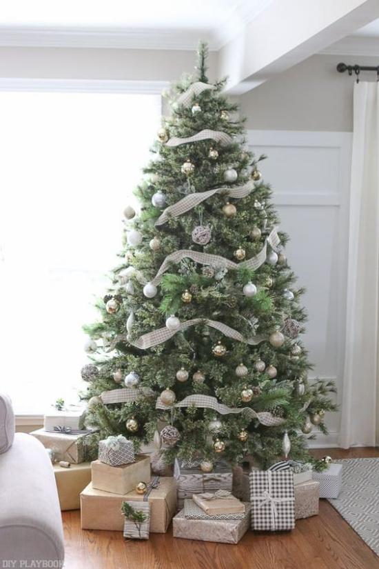 Weihnachtsbaum schmücken in Weiß und Silber viele Ornamente glänzende Girlanden