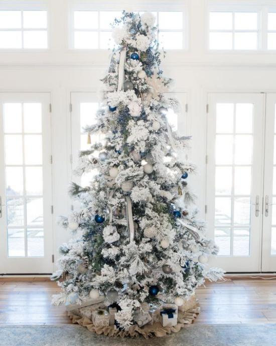 Weihnachtsbaum schmücken in Weiß und Silber vor dem Fenster platziert ein paar glänzende blaue Kugeln als Akzente