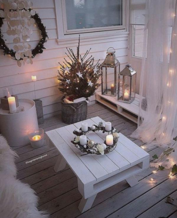 Weihnachtsdeko für Balkon ganz in Weiß zahlreiche Lichter und Kerzen Adventskranz auf einem niedrigen weißen Tisch in der Mitte