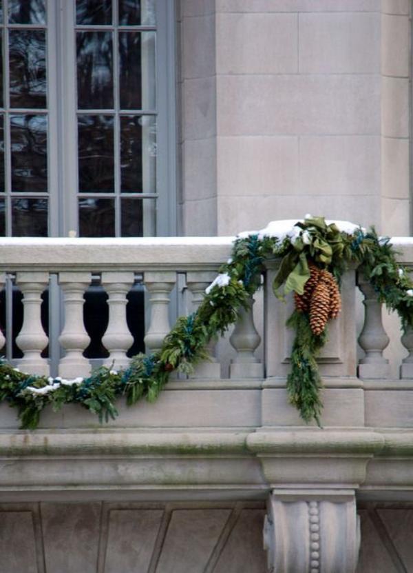 Weihnachtsdeko für Balkon grüne Girlande am Balkongelände Tannenzapfen