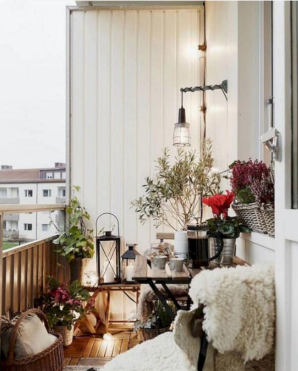 Weihnachtsdeko für Balkon verschiedene Topfpflanzen farbige Akzente setzen weiche Texturen weißer Pelz auf dem Stuhl viele Kerzen
