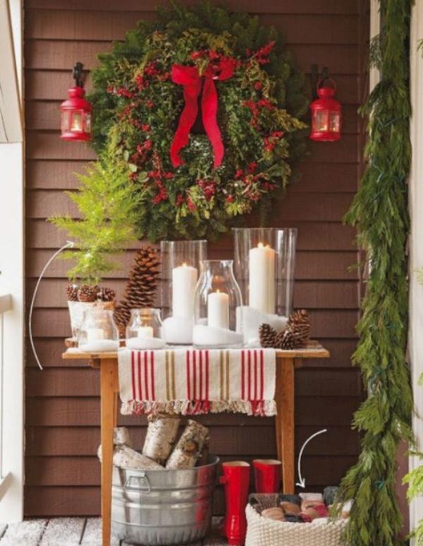 Weihnachtsdeko für Balkon viel Tannengrün rote Schleifen rote Stiefel weiße Kerzen gemütlich und ansprechend