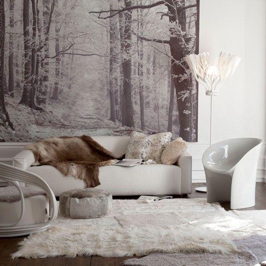 Winterdeko im Wohnzimmer Schneeweiß kuschelige Texturen in hellen Farben Schneelandschaft an der Wand ein gemütliches Ambiente sehr einladend