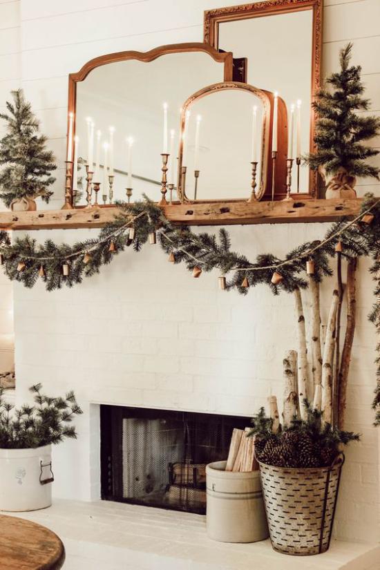 Winterdeko im Wohnzimmer am Kamin Spiegel elegante Kerzenständer Girlanden aus Tannengrün Eimer mit Tannenzapfen
