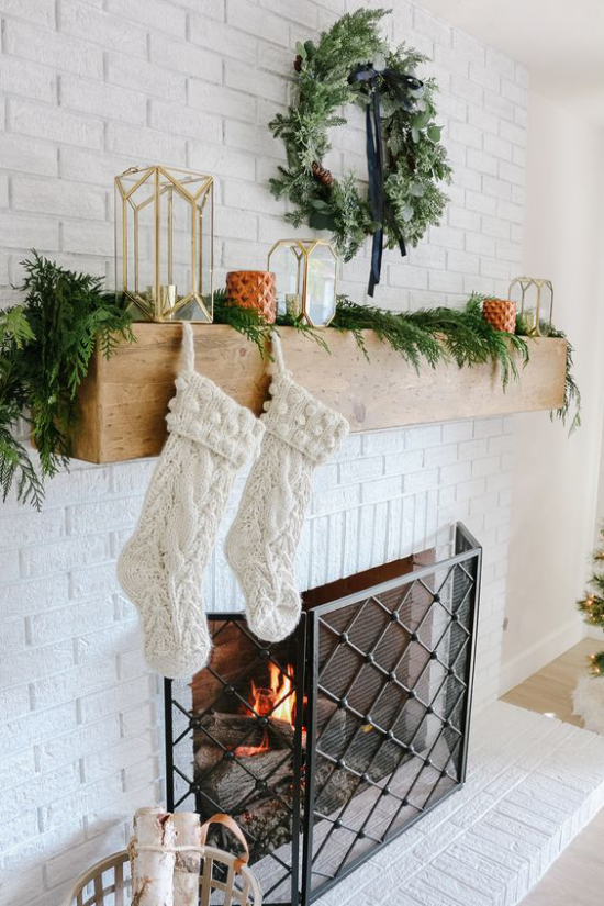 Winterdeko im Wohnzimmer am Kamin weiße Nikolausstrümpfe Tannengrün als Girlande kerzen Laternen Kranz an der Wand