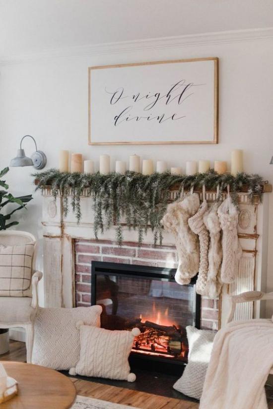 Winterdeko im Wohnzimmer brennder Kamin Nikolausstrümpfe etwas Tannengrün weiße Kerzen weiße Kissen