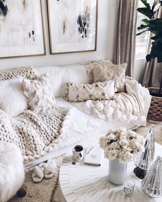Winterdeko im Wohnzimmer ganz in Weiß Decke Bezüge weiße Rosen auf weißem Kaffeetisch