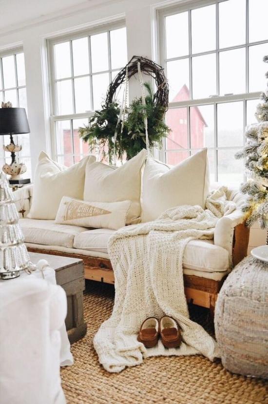 Winterdeko im Wohnzimmer ganz in Weiß gestaltet Strickdecke Kissen weißes Sofa rustikales Flair Kranz aus grünen Tannenzweigen am Fenster