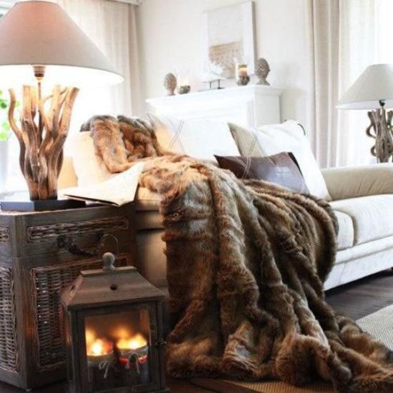 Winterdeko im Wohnzimmer gemütliche Atmosphäre viel Wärme Sofa mit heller Polsterung schokobraune warme Decke Laterne mit Kerzen Lampen