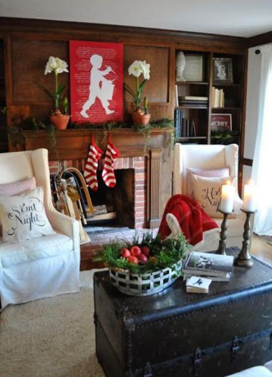 Winterdeko im Wohnzimmer klassische Farbkombination weiß rot grün weißer Sesselbezug natürliches Grün etwas Rot am Kamin
