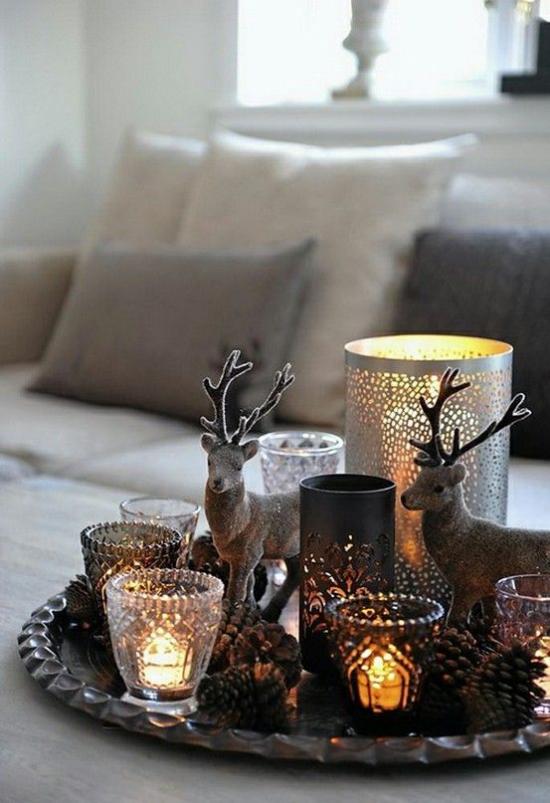 Winterdeko im Wohnzimmer meisterhaft arrangierte Kerzen Lichter Weihnachtsfiguren auf dem Kaffeetisch