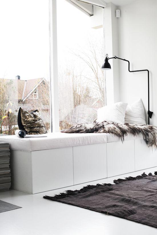 Winterdeko im Wohnzimmer sonnige Fensterecke zum Entspannen Kontrast weiß-schwarz weiche Kissen kuschelige Pelze Teppich