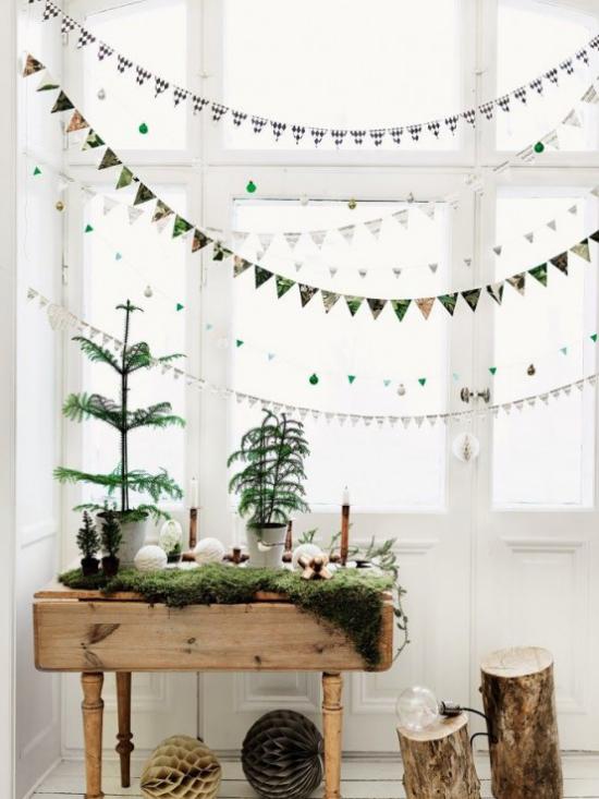 Winterdeko im Wohnzimmer viel Grün Girlanden und Lichterketten am Fenster rustikales Flair