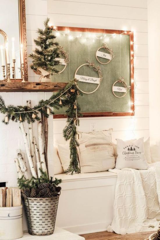 Winterdeko im Wohnzimmer weiße Sitzbank neben dem Kamin toll dekoriert mit einfachen Sachen etwas Grün Tannenzapfen im Eimer