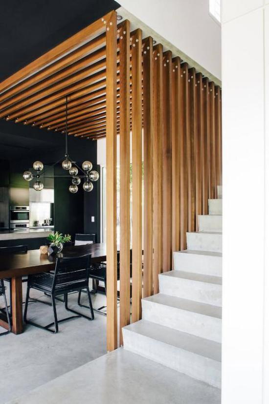 Akzente im Interieur setzen moderner Raumteiler aus Holz trennt das Esszimmer vom Treppenhaus