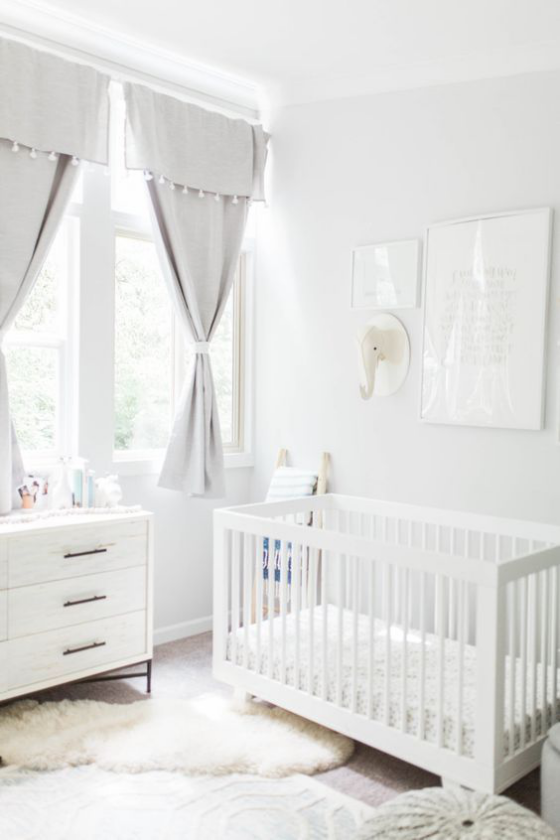 Babyzimmer in Weiß Kinderbett Kommode Gardinen viel Licht Fell auf dem Boden