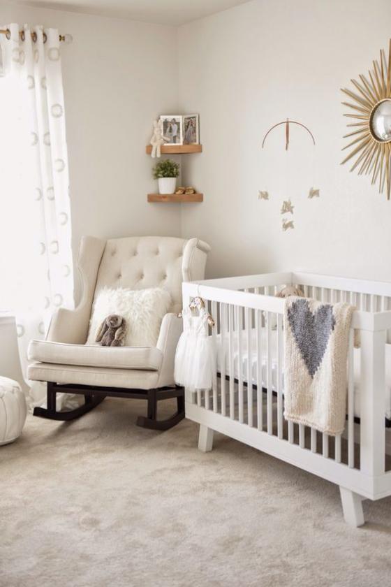 Babyzimmer in Weiß bequemer Sessel Babybett weiche Kissen Wurfdecken Wanddeko