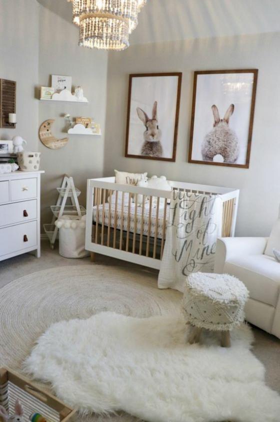 Babyzimmer in Weiß weiche Texturen wenig Wanddeko Hasenzeichnungen in Rahmen