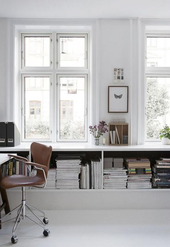 Homeoffice in neutralen Farben Bücherregal unter den Fenstern Lederstuhl viel Tageslicht