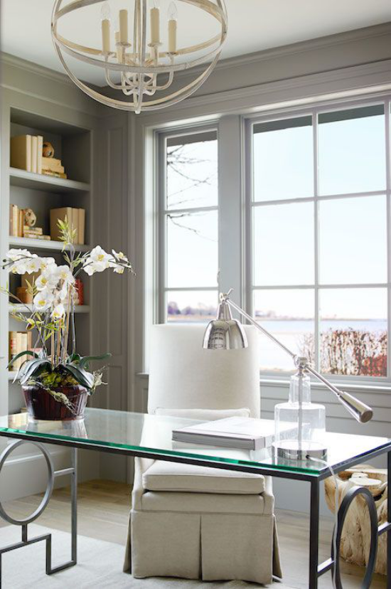 Homeoffice in neutralen Farben Tisch mit Glasplatte Orchidee elegante Lampe viel Tageslicht
