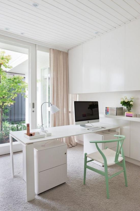 Homeoffice in neutralen Farben eleganter Tisch PC Stuhl im Pastellgrün Schreibtischlampe Blick nach außen