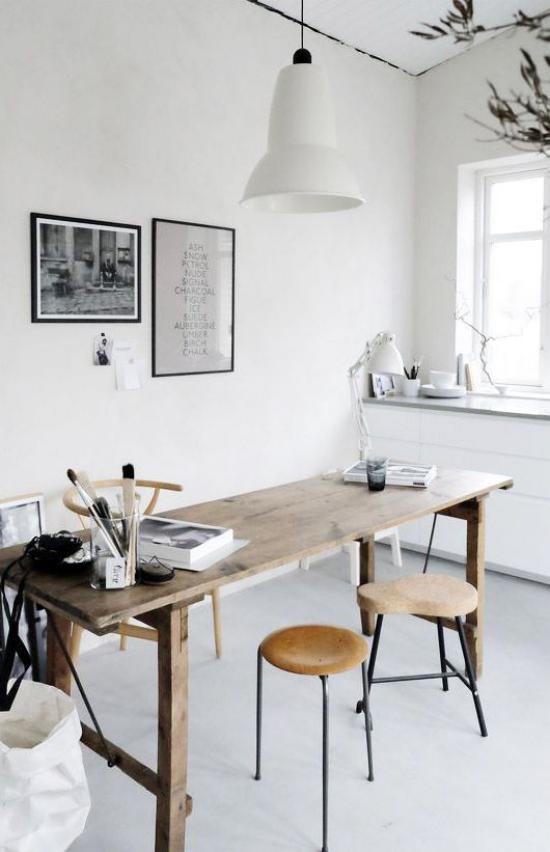 Homeoffice in neutralen Farben rustikales Ambiente Holztisch zwei Hocker Hängelampe Wandbilder