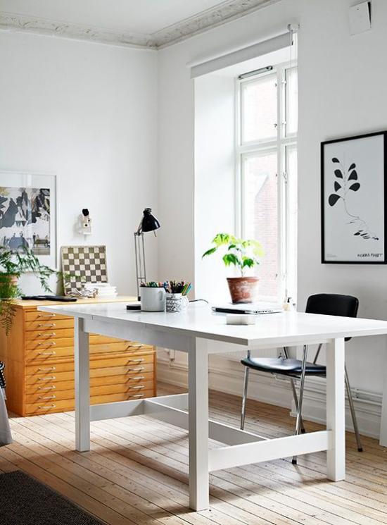 Homeoffice in neutralen Farben viel Tageslicht weißer Tisch kleine schwarze Lampe