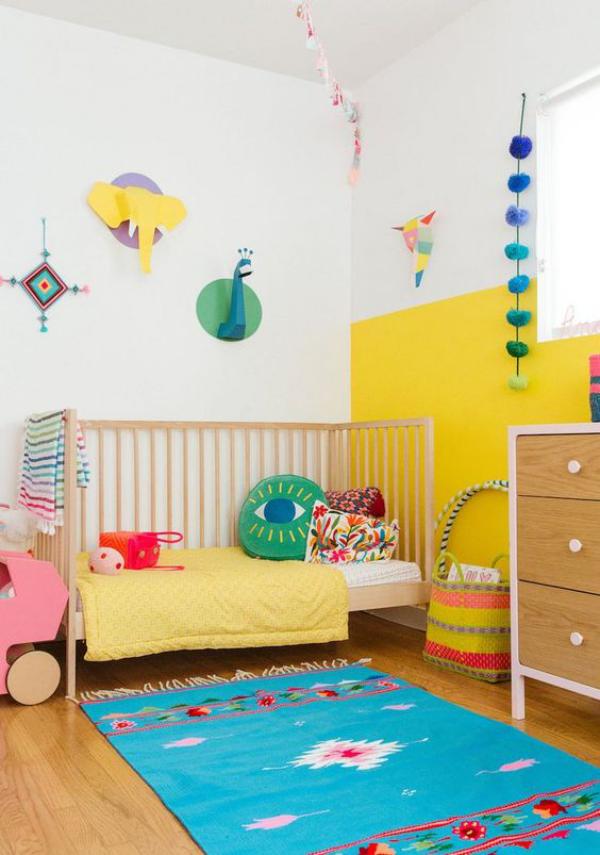 Kunterbuntes Babyzimmer blauer Teppich gelbe Wand Raumdekoration Bett bunte Kissen Babyspielsachen