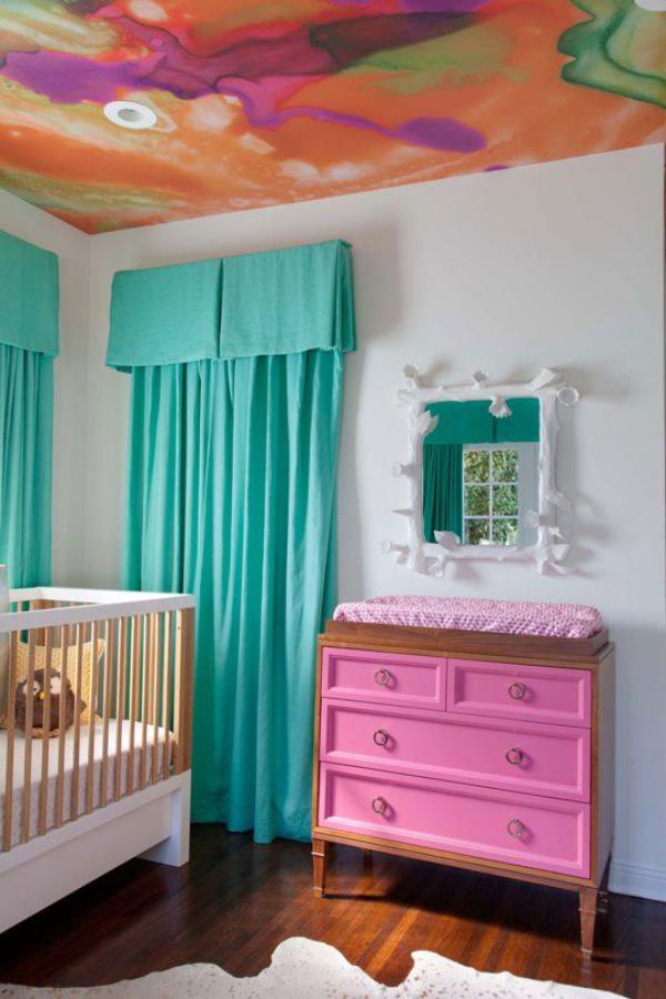 Kunterbuntes Babyzimmer bunt gestrichene Zimmerdecke türkisblaue Gardinen weißes Bett rosa Wickeltisch