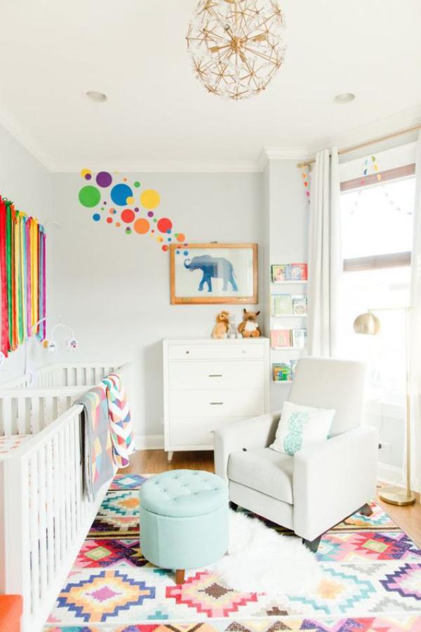 Kunterbuntes Babyzimmer bunter Teppich weißes Bett Sessel