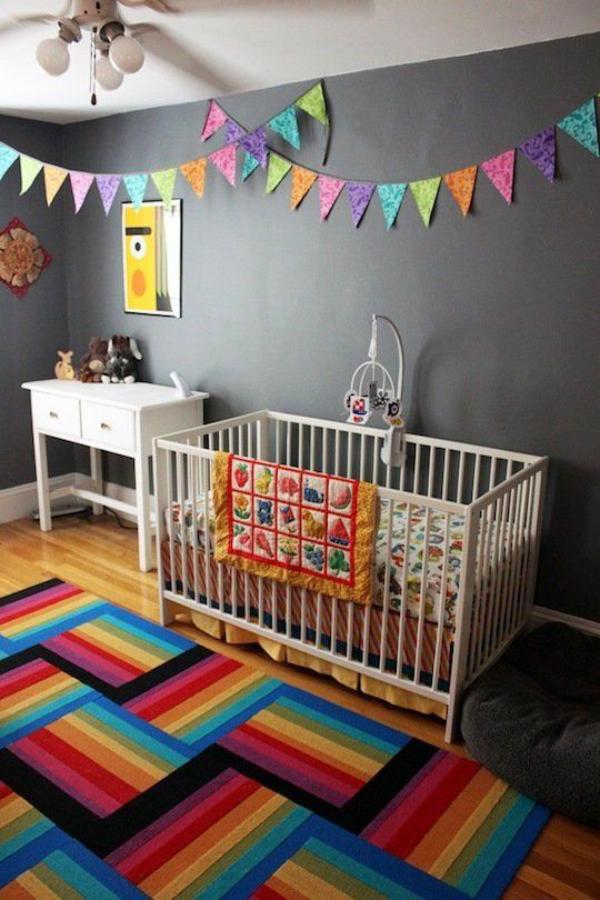 Kunterbuntes Babyzimmer dunkelgraue Wand aufpeppen bunte Girlanden farbenfroher Teppich