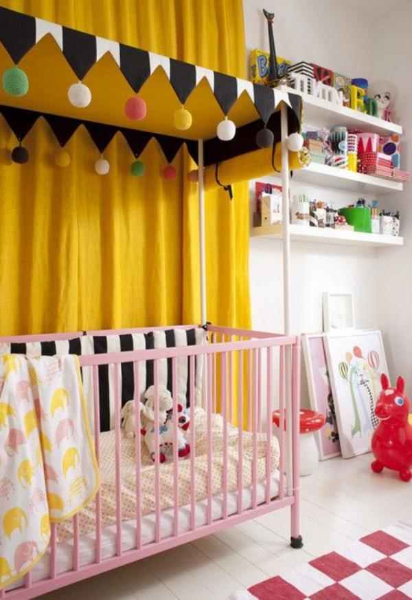 Kunterbuntes Babyzimmer gelbe Gardinen Girlande rosa Bett Regal Spielsachen