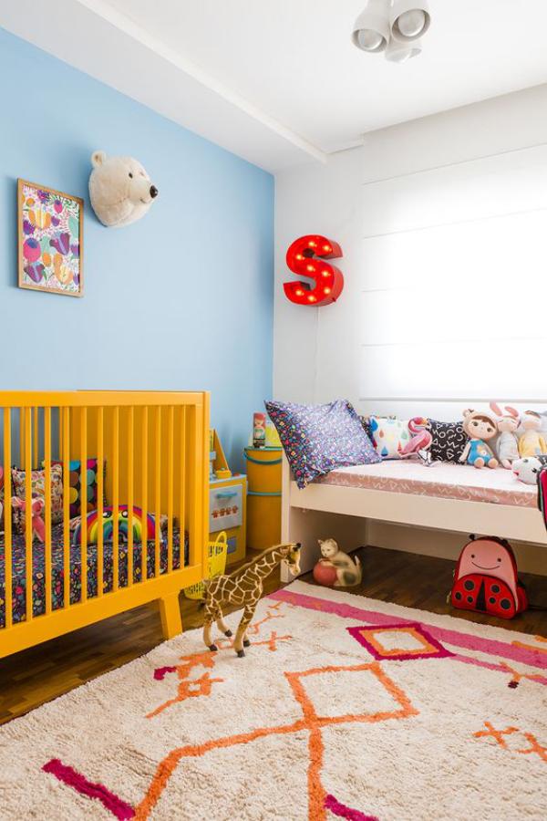 Kunterbuntes Babyzimmer gelbes Kinderbett blaue Wand weiße Wand weicher Teppich Wanddekoration Buchstabe