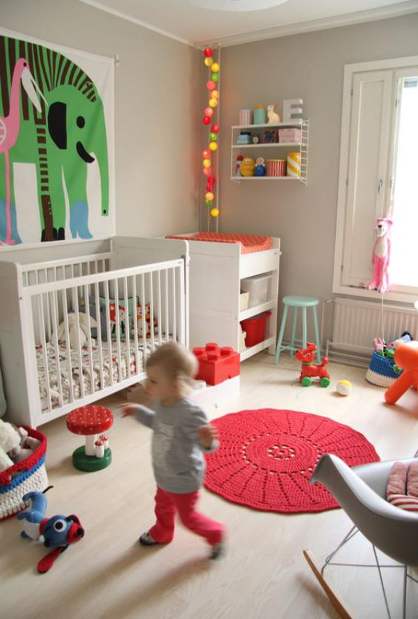 Kunterbuntes Babyzimmer roter runder Teppich gestrickt Baby spielt Wanddekoration