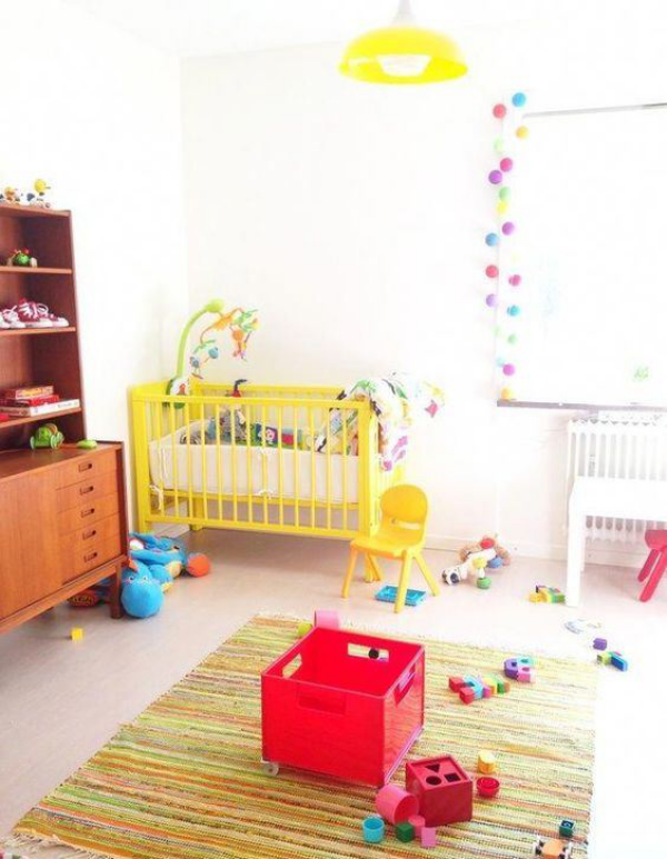 Kunterbuntes Babyzimmer viele Spielsachen Teppich Girlanden am Fenster gelbes Bett