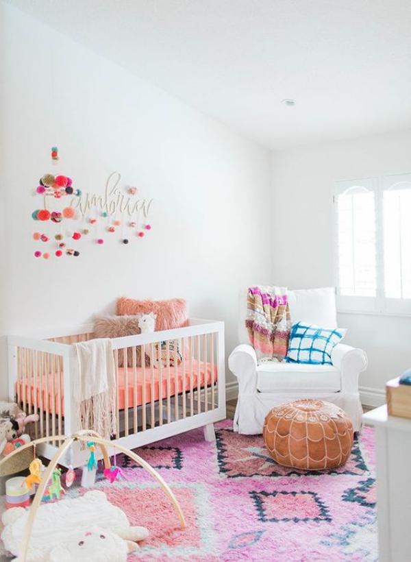 Kunterbuntes Babyzimmer weiße Wände weißes Kinderbett Teppich