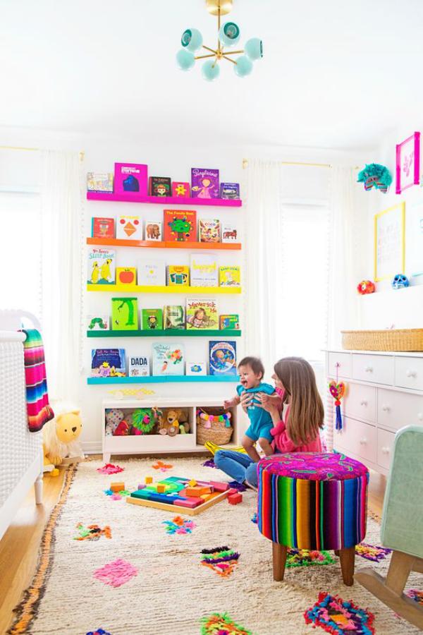 Kunterbuntes Babyzimmer weicher Teppich Regal bunte Bücher Spielsachen bunter Hocker