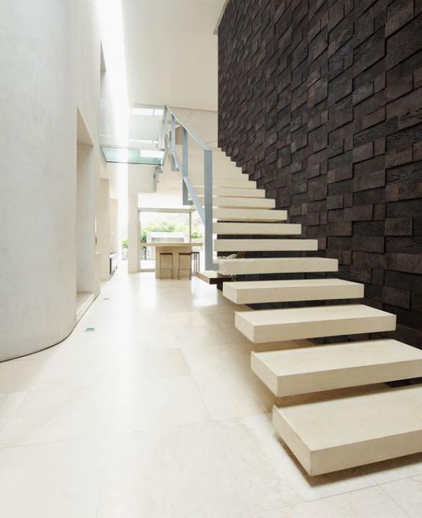 Leere Wand zum Hingucker machen dunkle Kork-Wandbeläge als Kontrast im elfenbeinfarbenen Raum